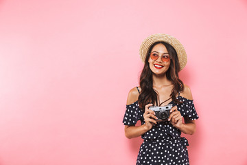 Smiling brunette woman in straw hat and sunglasses posing