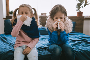 Being ill. Depressed young girls using paper tissues while being sick Wall mural