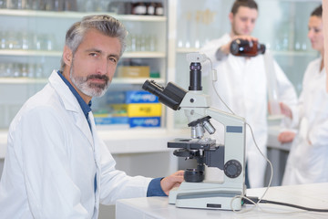senior male scientist or tech observes sample under the microscope
