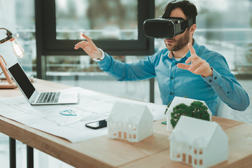 Virtual reality. Nice pleasant man using 3d glasses while working in the office
