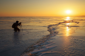 Photographer take pictures on the ice during sunset