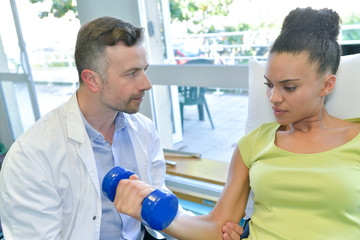 therapist doing arm exercises with dumbbells for improving arm strenght