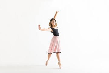 Confident Young Ballerina Dancing Gracefully On White Background
