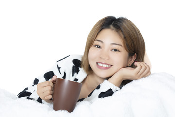 Chinese woman laying in bed drinking coffee on white background