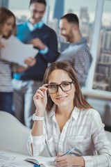 Smart employee. Confident female colleague taking notes and touching glasses