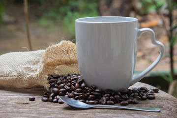 Cup of coffee with smoke and coffee beans in burlap sack on wooden table and blurred tree background.