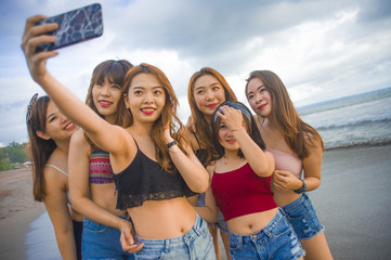 lifestyle beach portrait of Asian Korean and Chinese women, group of happy beautiful young girlfriends taking selfie picture together with mobile phone
