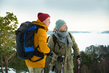 Two mature men with exploring Finland in winter. Travellers hiking and Taking pictures with camera on the top of rock. Beautiful view of northern landscape with frozen Baltic Sea and snowy islands.