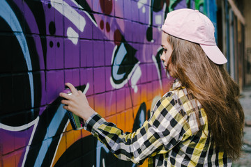 Young woman graffiti artist drawing on the wall, outdoor