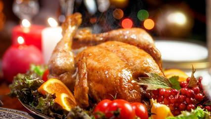 Hot baked chicken from oven on family festive dinner table on Christmas eve