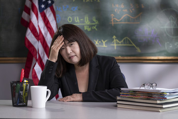 Portrait of a stressed teacher in her classroom