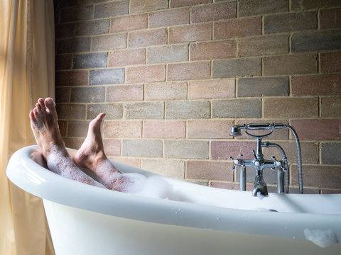 Men's  feet covered with foam bubble bath  in luxury bathtub with happiness and relaxing