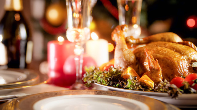 Beautiful served table for family Christmas dinner at burning fireplace
