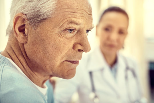 Depressive time. Pensive elderly man looking into vacancy and thinking while attending his female doctor for a checkup.