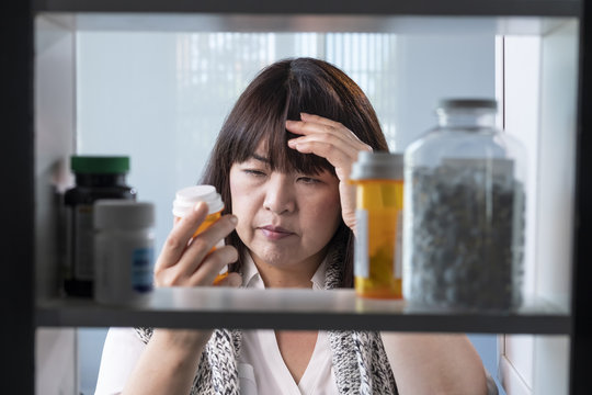 Woman looking at prescription drugs in her medicine cabinet