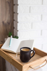 A cup of coffee and an open notebook on a wooden tray in the light interior of the apartment. Cozy home