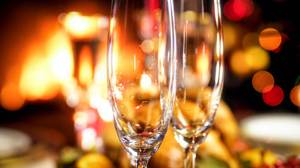 Closeup image of two empty champagne flutes against burning fireplace