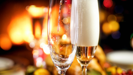 Closeup image of champagne flowing in two glasses against burning fireplace