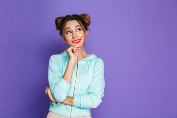 Portrait of european brunette girl with two buns looking upward on copyspace and touching chin, isolated over violet background in studio