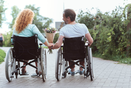 Supportive relations. Turned back husband and wife sitting in wheelchairs and looking at each other while holding flowers together.