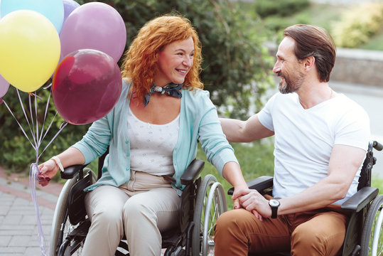 Support is what really matters. Cheerful husband and wife sitting in wheelchairs and grinning broadly while holding balloons and chatting.