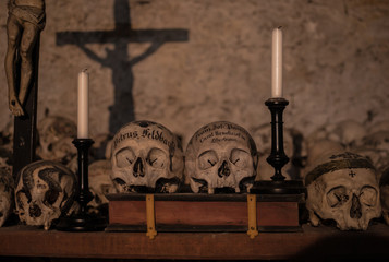 Decorated skulls in the Parish Church of Hallstatt. Vintage candlesticks and crucifix casting shadows on the wall of the crypt