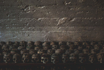 Decorated skulls in the Parish Church of Hallstatt. Multiple skulls covered with spider web and dust in the ossuary