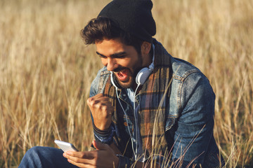 Young happy man using a smartphone in nature