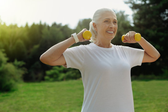 Stronger than yesterday. Waist up shot of a full of energy retired woman grinning broadly while lifting dumbbells during a workout outdoors.