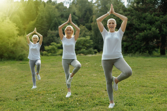 Calm and collected. Full length shot of three senior women standing in a balancing pose while exercising outdoors and practicing yoga together.