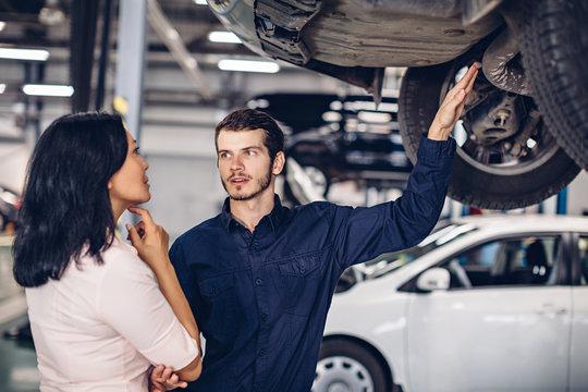 Auto car repair service center. The mechanic communicates with the client