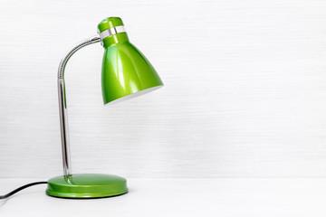 Green lamp on wooden desk