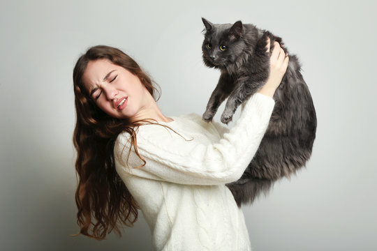 Young woman with allergy holding cat on grey background