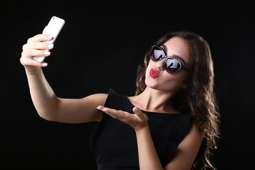 Young woman sending kiss and making selfie on black background