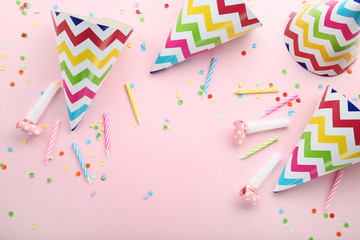 Birthday paper caps with candles and blowers on pink background