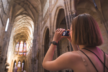 Tourist girl makes a photo of an interior on a smartphone in the old historic church.Girl stands in the temple and photographs church.Tourist photographed interior in St.Vitus Cathedral,Prague