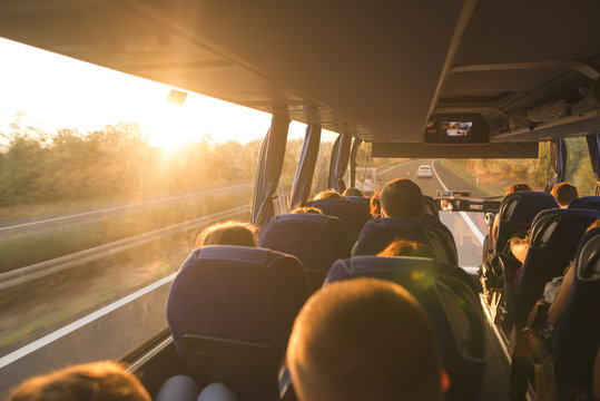 Background. Travel by bus. Bus interior. Salon of the bus with people fill the sun with light in the sunset. People travel on a big tourist bus. The bus rides along the mornings in the sunrise