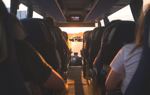 People ride in the bus at sunset. Salon bus with tourists. Selective focus of the bus interior with tourists at sunset.