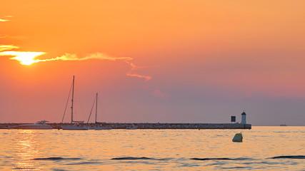 Sonnenuntergang an der Küste von Porec in Kroatien. Im Hintergrund der Leuchtturm der Insel Sveti Nikola.