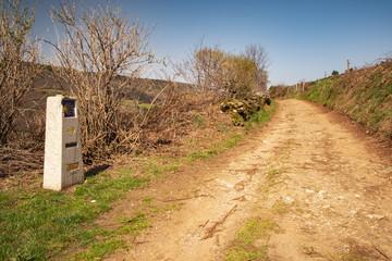 Der Jakobsweg nach Triacastella - Links im Bild, ein Wegweiser der die Richtung und Entfernung nach Santiago de Compostela anzeigt
