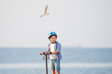 cute healthy kid in helmet on scooter on sea with flying seagull bird background