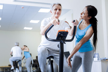 Nice activity. Kind attentive qualified trainer looking at her energetic recovering patient on an exercise bike and smiling while noticing his progress
