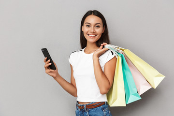Cheerful woman holding shopping bags isolated over grey background using mobile phone.
