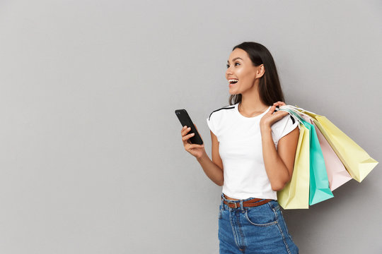 Cheerful woman holding shopping bags isolated over grey background using mobile phone looking aside.