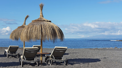 Relaxing spot on the pebble beach of Playa de la Enramada with two thatched umbrellas and four chaise lounges with views towards La Gomera Island, in the south of Tenerife, Canary Islands, Spain