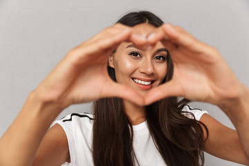 Woman isolated over grey background showing heart love gesture.