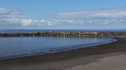 Playa del Duque, new black sand extension beach, early morning, with calm waters and no tourists yet, in Tenerife, Canary Islands, Spain
