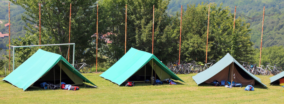 three green tents mounted by scouts in a meadow