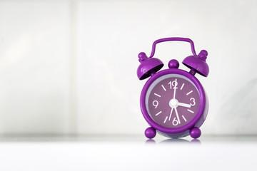 Purple alarm clock in a bright room