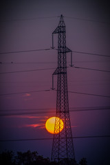 Poste de electricidad de voltaje y línea de conducción eléctrica de transmisión sobre el cielo azul y fondo de nubes blanco.